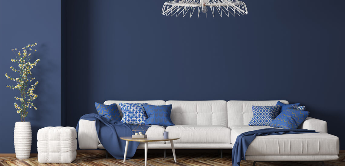 White furniture with blue walls and accent pillows
